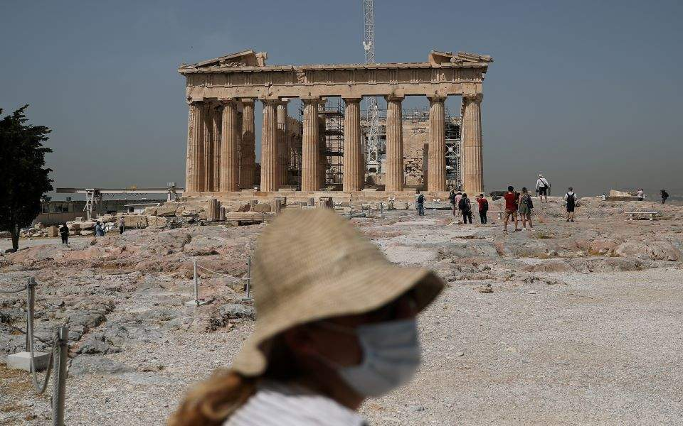 A masked woman in front of Parthenon, source: ekathimerini